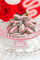 A glass bowl of sugared dates stuffed with pink marzipan