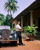 SRI LANKA, Asia, Galle,  portrait of a driver standing by vintage car in front of the Dutch House Hotel.