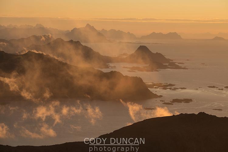 Autumn mist forms over mountains at sunrise from Tønsåsheia, Lofoten Islands, Norway