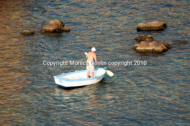 A man rowing a white boat just outside the city walls of Dubrovnik, Croatia.