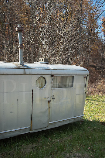 Silver mobile home trailer parked in the grass, abandoned, old, worn, and dented.