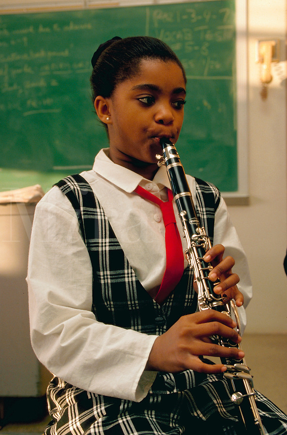 Young African-American girl playing a clarinet in school.