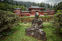 A Buddha statue sits in front of a large koi (fish) pond at the Byodo-In Temple in Windward O'ahu.