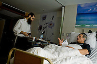 Rabbi Goldshmid brings donuts and tefillin to a hospital in Koh Samui, to visit Erez Levanon, the owner of a spa (with partner Dali, photographed in spa), who has been in the hospital for 5 days. Photo by Suzanne Lee / For Chabad Lubavitch
