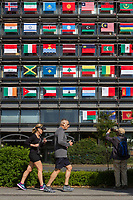 Joggers run in front of the Offices of the Mainichi Newspaper Company display all 206 flags of the countries taking part in the 2020 Tokyo Olympic Games. Chiyoda, Tokyo, Japan. Friday October 27th 2017. Saturday October 28th marks 1,000 days before the opening ceremony of the Summer Olympics in Tokyo. Each flag is 210 centimeters wide and 140 centimeters high and is being draped over windows on the south side of the building, facing the Imperial Palace