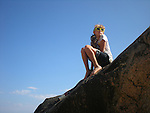 Girl with yellow sunglasses on ocean rock against blue sky.<br /> Mohegan Bluffs, Block Island