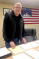 Sally Carroll/McDonald County Press<br /> Gregg Sweeten reviews and organizes paperwork resulting from two floods in McDonald County. Sweeten's job as emergency management director includes overseeing a great deal of paperwork, in addition to monitoring weather situations.
