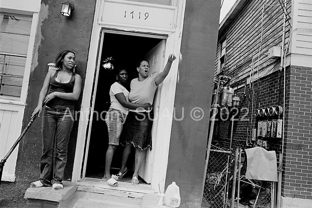 New Orleans, Louisiana.USA.July 29, 2006..Juanita Thomas, an aunt of three of the slain victims, shouts at Darryl McDaniel, the father of two of the victims, outside her home saying that he wasn't a good father...A quadruple homicide in the city center happened at this spot the night before. Crime is on the rise as residents return looking for work and living in questionable housing conditions. Younger drug lords try to claim territory in the destroyed New Orleans districts nearly one year after hurricane Katrina hit and the levees broke leaving 90% of the city flooded. .