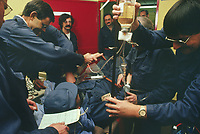 Switzerland. Canton Lucerne. Medical exercice in the emergency hospital of the Sonnenberg tunnel in Lucerne  during the largest civil defense exercise ever held in the country. A man is lying wounded on a stretcher and is checked by a doctor and several nurses. The man has received a drip. From 16 to 21 November 1987, almost 1200 men and women converted a motorway tunnel into perhaps the world's largest bunker structure. The civil protectors had to prove during the exercise «Ameise» ( Ants in english) that in an emergency more than 20,000 inhabitants of the city of Lucerne could survive here in the mountain for two weeks. The Sonnenberg Tunnel is a 1,550m  long motorway tunnel, constructed between 1971 and 1976. At its completion it was also the world's largest civilian nuclear fallout shelter, designed to protect 20,000 civilians in the eventuality of war or disaster. Based on a federal law from 1963, Switzerland aims to provide nuclear fallout shelters for the entire population of the country. The construction of a new tunnel near an urban centre was seen as an opportunity to provide shelter space for a large number of people at the same time. The giant bunker was built between 1970 and 1976 at a cost of 40 million Swiss francs. The shelter consisted of the two motorway tunnels (one per direction of travel), each capable of holding 10,000 people in 64 person subdivisions. A seven story cavern between the tunnels contained shelter infrastructure including a command post, an emergency hospital, a radio studio, a telephone centre, prison cells and ventilation machines. The shelter was designed to withstand the blast from a 1 megaton nuclear explosion 1 kilometer away. The blast doors at the tunnel portals are 1.5 meters thick and weigh 350 tons. The logistical problems of maintaining a population of 20,000 in close confines were not thoroughly explored, and testing the installation was difficult because it required closing the motorway and rerouting the usual t