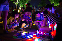 A street vendor sells colorful lightup toys as people gather to watch the nightly musical fountain and light show outside the Dayan Pagoda (Big Wild Goose Pagoda) in Xian, Shaanxi, China.