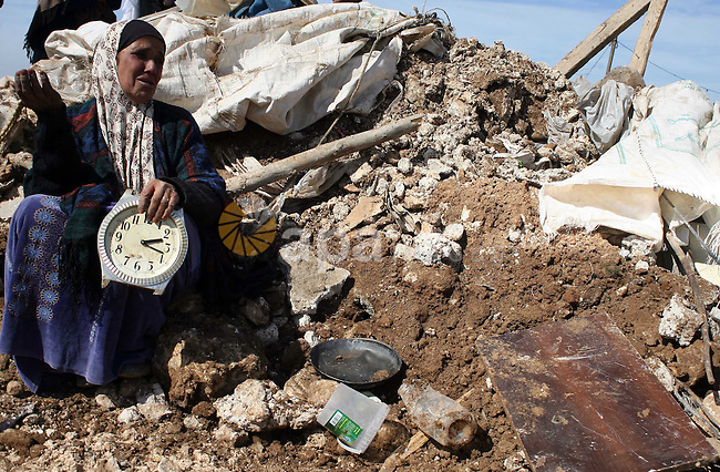 Members of a Palestinian family retrieve items from the rubble of their home after it was destroyed by Israeli army tractors early on 22 February 2011 in the West Bank village of Yatta near Hebron. The house was located in the so-called Area C, a closed military zone where Israel exercises full control and was built without permission, according to the Israeli army. Photo by Najeh Hashlamoun