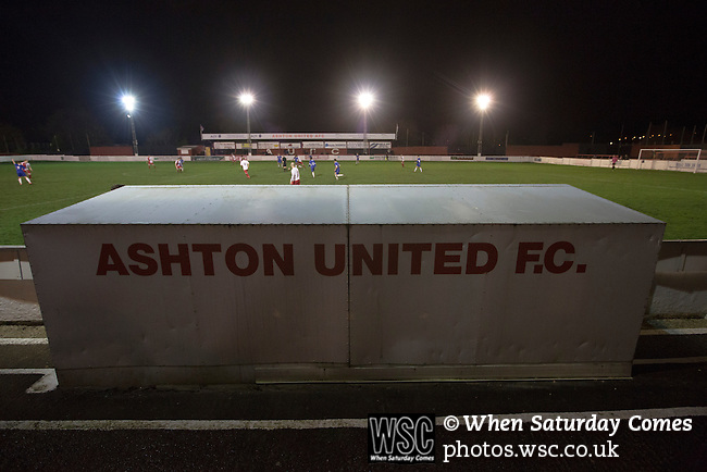 Ashton United 6 Ramsbottom United 0, 12/01/2016. Hurst Cross stadium, Northern Premier League. The home team dugout dominates the scene during the second-half of the fixture between Ashton United (in red) and Ramsbottom United in the Northern Premier League premier division. The match was played at Ashton's Hurst Cross stadium, the club's ground. The club was originally founded in 1878 as Hurst F.C. and by 1880 the club were playing at Hurst Cross, their current ground which makes their home one of the oldest football grounds in the world. Ashton won the match 6-0, watched by a crowd of 178. Photo by Colin McPherson.