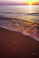 SUNSET OVER LAKE SUPERIOR BEACH IN ONTONAGON MICHIGAN WITH WAVE ACTION AND STONES.