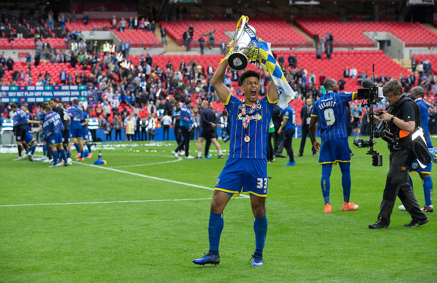 AFC Wimbledon's Lyle Taylor celebrates with the winner's trophy<br /> <br /> Photographer Craig Mercer/CameraSport<br /> <br /> Football - The Football League Sky Bet League Two Play-Off Final - AFC Wimbledon v Plymouth Argyle - Monday 30 May 2016 - Wembley Stadium - London<br /> <br /> World Copyright &copy; 2016 CameraSport. All rights reserved. 43 Linden Ave. Countesthorpe. Leicester. England. LE8 5PG - Tel: +44 (0) 116 277 4147 - admin@camerasport.com - www.camerasport.com