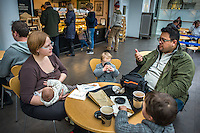A mother with her family breastfeeding her baby while talking to the dad in a museum cafe.<br /> <br /> London, England, UK<br /> 08/03/2015<br /> <br /> &copy; Paul Carter / wdiip.co.uk