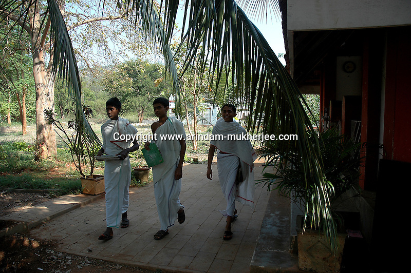 Students of Om Shantidhama going to morning school. Om Shantidhama is a residential vedic school for boys. Nestled among the confluence of hills, forest and rivers - Om Shanti Dhama is a world removed from the maddeningly fast and often chaotic urban India. Students from allover the country are selected to take part in its Vedic and free education system. What is unique about this institute is that they have blended the traditional and modern education system. Here computer and science is taught with the same passion as the Vedas and Shastras, helping the students to grow spiritually as well as earn a living. Bonding with the nature and animal world is a mandatory part of the institute's curriculum. Karnataka, India. Arindam Mukherjee