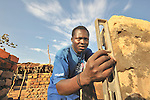 Jackson Batal checks the plumb of a brick wall in the Southern Sudan village of Kupera. Families here are rebuilding their homes after returning from refuge in Uganda in 2006 following the 2005 Comprehensive Peace Agreement between the north and south. NOTE: In July 2011, Southern Sudan became the independent country of South Sudan