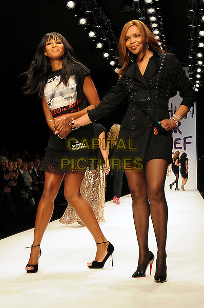 NAOMI CAMPBELL & VALERIE CAMPBELL.The Fashion For Relief Haiti 2010 show for London Fashion Week Autumn/Winter 2010 at Somerset House, London, England..February 18th, 2010.LFW catwalk runway full length black t-shirt lace dress holding hands mother mom mum daughter family  .CAP/CAS.©Bob Cass/Capital Pictures.