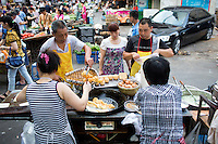 Cooks prepare you tiao, or oil sticks, at a food stand in a morning market in a residential area in western Jiangbei District, Chongqing, China.