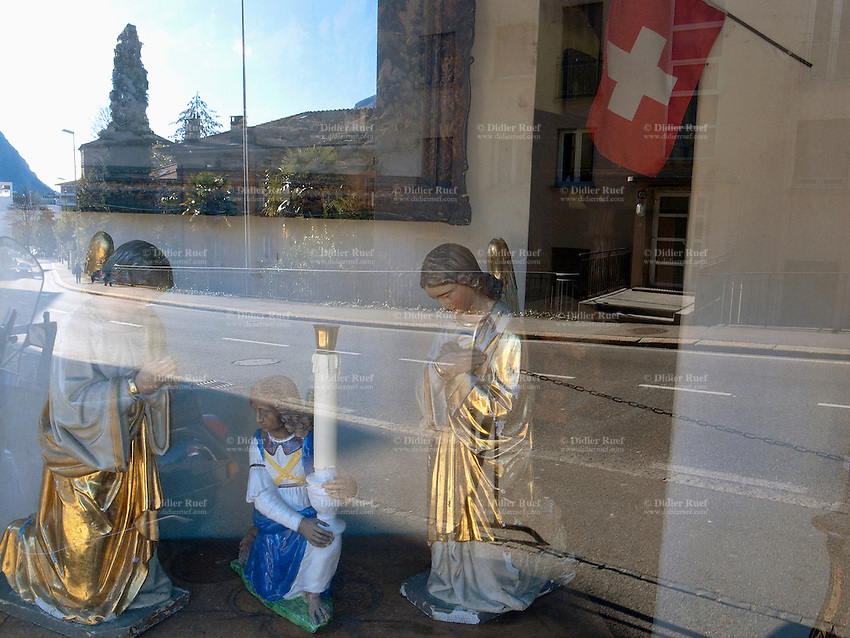 Switzerland. Canton Ticino. Lugano. Shop window of an antique store with religious scenes and sculptures for sale. Electric candle. Swiss flag. 20.01.11 © 2011 Didier Ruef