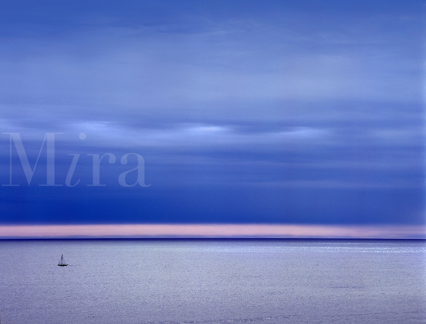 Sailboat crossing a large expanse of open blue water at dusk. Acadia National Park, Mount Desert Island, Maine