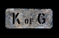 A rusting metal tag is punched with the initials for the Knight of Glin