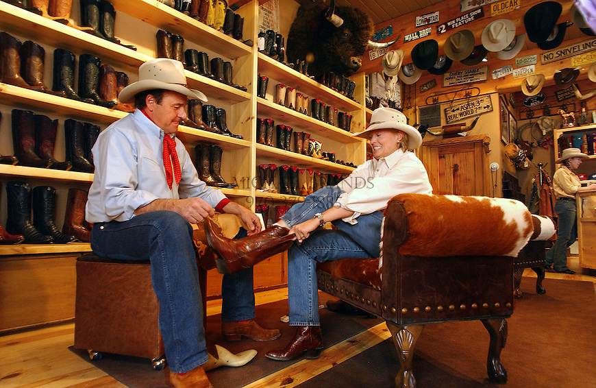 Trying on a paid of cowboy boots at Kemosabe in Aspen, Colorado. © Michael Brands. 970-379-1885.