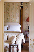 A glimpse through an open door to an elegant four-poster bedroom