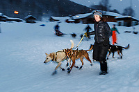 Trail crew volunteer Michele Phillips walks Cindy Gallea's dogs down the trail to leave after Cindy's 24-hour layover in the morning at the Takotna checkpoint on Friday March 8th during the 2019 Iditarod Trail Sled Dog Race.<br /> <br /> Photo by Jeff Schultz/  (C) 2019  ALL RIGHTS RESERVED