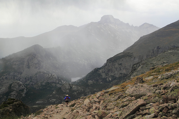 Hiker walking towards Longs Peak during a thunderstorm on the Flattop Mountain Trail, Rocky Mountain National Park, west of Estes Park, Colorado.