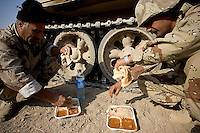 Iraqi tankers from the 1st company, 1st armour battalion of the 1st mechanized Iraqi Army Brigade eat their lunch during an Observation posts mission   while conducting  patrols, check points and observation posts on code name route Michigan, the main road of Ramadi in the week during the national election on TUE Dec 13 2005 in Ramadi, Iraq. 1st company is part of the first armor battalion of the New Iraqi Army. it has started its training in January 2005. after 50 days their 35 russian and chinese built T 55 tanks begun conducting operations under the guidance of a US military adivisor team. in April 2005 they patrolled in the Abu Ghraib area concluding their first significant mission. While these old tanks are rolling on the ramadi streets more modern T72s are getting ready to become fully operational in Taji, their main base. the Iraqi army wanted to show their power in ramadi during the Dec 15 elections displaying their new armour company. but like all the other Iraqi forces they are not going to secure the polling sites, staying in the rear with the rest of the iraqi and coalition forces. T 55s are very old tanks. production begun in the late 50s to the late 70s. athough obsolete many countries still use the T55 as their main heavy armoured combat vehicle. slow, heavvy and with very little room for the crew it suffers from many mechanical problems constantly challenging the iraqi mechanics and engineers.