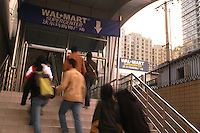 Beijing shoppers step out of a train station and directly onto a ramp that leads to the Beijing Wal-Mart on November 6, 2005.