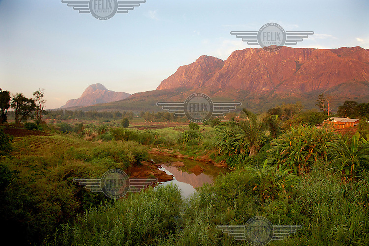 Mulanje Mountain rises above a river and cultivated fields.