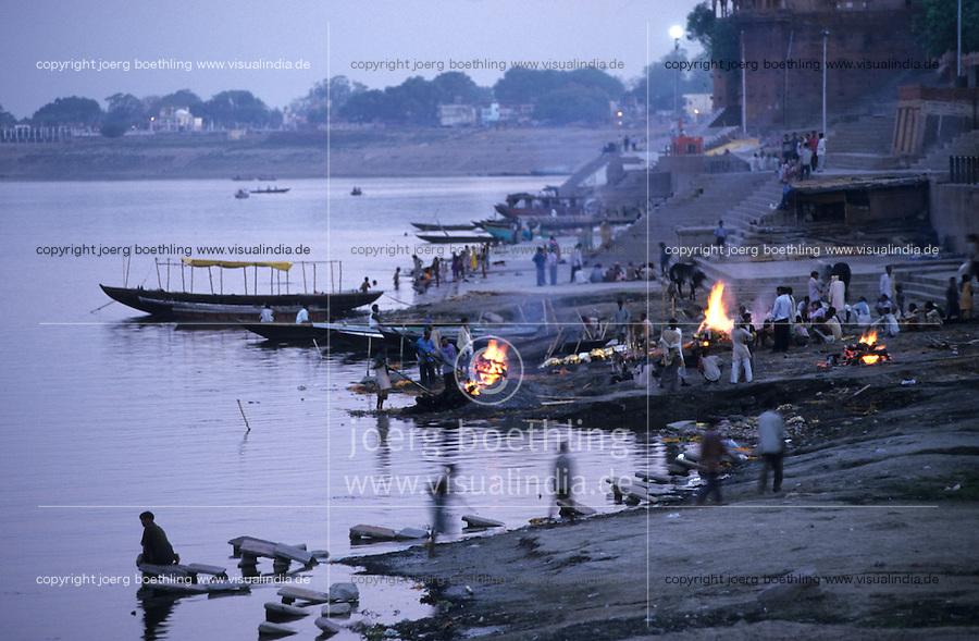 INDIA Varanasi, cremation of dead body at  at river Ganga , it is part of ritual moksha hindu belief to come into heaven and get salvation of rebirth here / INDIEN Benares Varanasi Kashi , die Doms, unberuehrbare Kaste der Bestatter verbrennen die Toten auf Scheiterhaufen aus Holz am Manikarnika Ghat, Hindus glauben an Moksha, wer in Benraes stirbt oder verbrannt wird, entgeht dem Kreislauf der ewigen Wiedergeburten und kommt in den Himmel