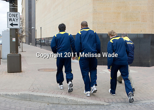 A.J. Treais (Michigan - 21), Scooter Vaughan (Michigan - 3) and Lindsay Sparks (Michigan - 39) leave their teammates behind. - The University of Michigan Wolverines walked to the Xcel Energy Center from their hotel for an autograph session prior to the Hockey Humanitarian and Hobey Baker award ceremonies on Friday, April 8, 2011, at the 2011 Frozen Four in St. Paul, Minnesota.