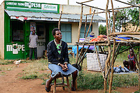 KENIA, County Siaya, village Kotanega, shop M-Pesa, of company Safari.com a joint venture of Vodafone and kenyan telephone, payment by mobile phone, market woman sells vegetables / KENIA, bezahlen per Mobiltelefon, M-Pesa von Safari.com a joint venture von Vodafone and kenyan telephone, Marktfrau verkauft Gemuese