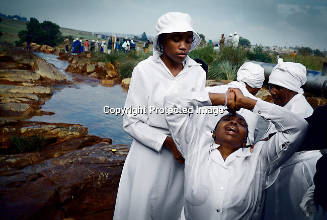 SOWETO, SOUTH AFRICA MARCH 27: Unidentified women from Eastern Baptist Zionist Church pray during an outdoor service on March 27, 2005 close to Orlando West in Soweto, Johannesburg, South Africa. They celebrated Easter weekend in Soweto, South Africa?s largest township. It was founded about one hundred years ago to make housing available for black people south west of downtown Johannesburg. The estimated population is between 2-3 million. Many key events during the Apartheid struggle unfolded here and the most known is the student uprisings in June 1976, where thousands of students took to the streets to protest that they had to study the Afrikaans language at school. Soweto today is a mix of old housing and newly constructed townhouses, and a new hungry black middle-class is growing steadily. Most residents work in Johannesburg but the last years many shopping malls has been built, and people are starting to spend their money in Soweto. (Photo by Per-Anders Pettersson)