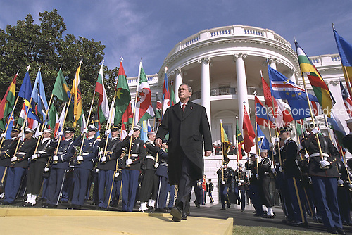 Walking past flags representing countries supporting America's fight against terrorism, United States President George W. Bush approaches the podium during a South Lawn ceremony on the six-month anniversary of the September terrorist attacks at the White House in Washington, D.C. on Monday, March 11, 2002..Mandatory Credit: Paul Morse - White House via CNP.
