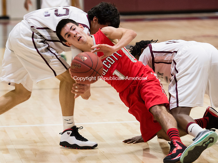 NAUGATUCK, CT - 29 December 2015-122915EC04--   Wolcott's Bobby White passes to a teammate as he gets tangled up with Naugatuck's (12) Andre Trosan and (35) Fejiro Onakpoma Tuesday night in Naugatuck. Erin Covey Republican-American.
