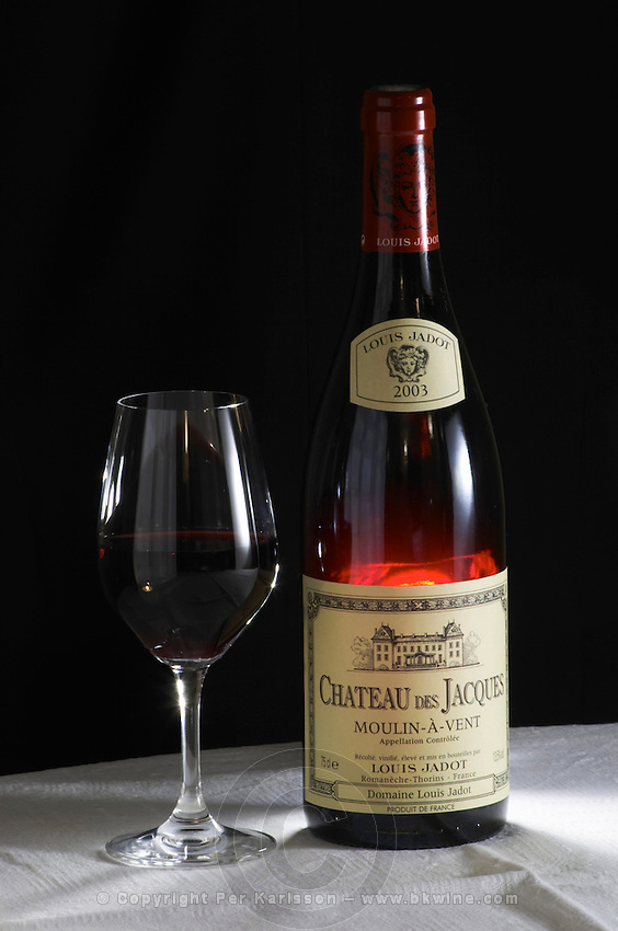 A bottle of Maison Louis Jadot Chateau des Jacques Moulin-a-Vent Beaujolais 2003 red burgundy wine and a glass of red wine standing on a table top with a white cloth. Backlit backlight back light lit Black background, Maison Louis Jadot, Beaune Côte Cote d Or Bourgogne Burgundy Burgundian France French Europe European