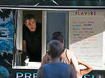 "Philip Velasquez serves customers in his ""Black Ice"" shaved ice trailer during Sizzling Saturdays Food Truck event in Sparks on Saturday, July 20, 2019."