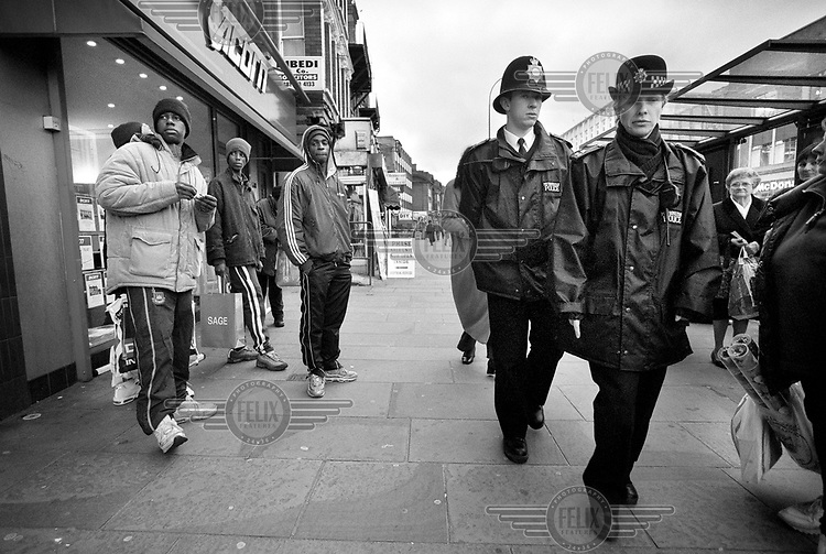 Two uniformed police officers pass a group of youths as they patrol Lewisham High Street.