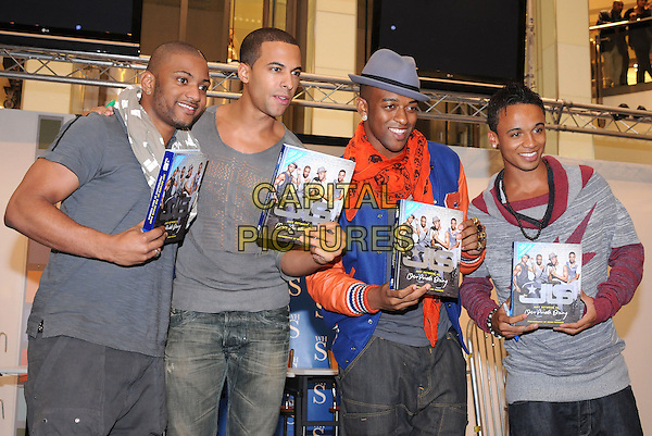 """JLS - JONATHAN 'JB' GILL, MARVIN HUMES, ORTISE WILLIAMS, ASTON MERRYGOLD.JLS Sign Copies Of Their New Book """"Just Between Us, Our Private Diary"""" At Lakeside Shopping Centre, Essex, England, UK, 28th September 2010..half length boy band group hat grey gray top t-shitr jeans Alexander Mcqueen skull scarf orange red print blue jacket .CAP/BRC.©Ben Rector/Capital Pictures."""