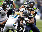 Seattle Seahawks running back Marshawn Lynch is stopped by Jacksonville Jaguars Josh Evans (26) and Paul Posluszny (51) for a short gain at CenturyLink Field in Seattle, Washington on September 22, 2013. The Seahawks beat the Jaguars 45-17. ©2013. Jim Bryant Photo. ALL RIGHTS RESERVED.