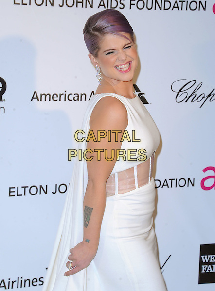 Kelly Osbourne  .The 21st Annual Elton John AIDS Foundation Academy Awards Viewing Party held at The City of West Hollywood Park in West Hollywood, California, USA..February 24th, 2013.oscars half length white sleeveless dress hand on hip sheer cape tattoos cut out panel waist smiling side .CAP/DVS.©DVS/Capital Pictures.