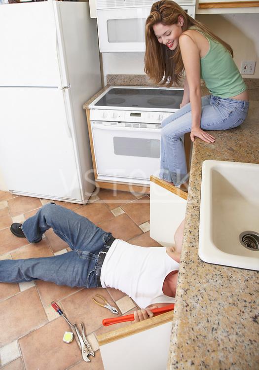 Young woman watching plumber fixing kitchen sink