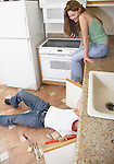 Young woman watching plumber fixing kitchen sink