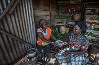 Uganda, Naalya Main.Rosette Kyomuhangi uses the BioLite stove for her busienss to make breakfast for customers like Rose Namirembe.