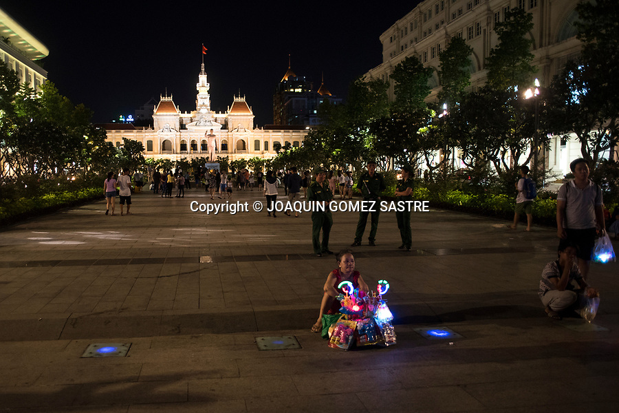 A woman with her toy stall in Ho Chi Minh City Hall (in the background) today became the seat of the popular committee<br /> HO CHI MINH-VIETNAM