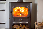 Warm fire flames logs burning in ClearView domestic multifuel stove burner inside home, UK